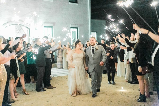 plus size bride and groom doing having a sparkler exit